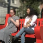 Two women sit on a red bench and calmly listen to the sounds of their heartbeats.