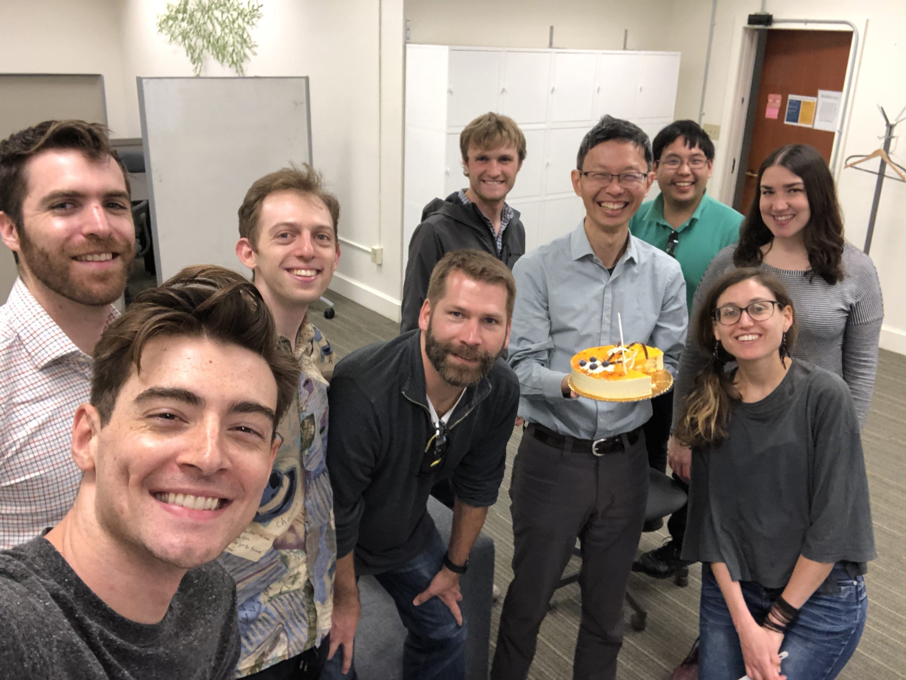 People gathered around smiling and John is holding a cake.